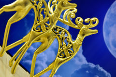 Gold figures of stags in the background of the moon Stock Photos