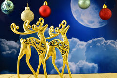 Gold figures of stags in the background of the moon Stock Images