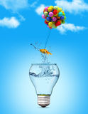 Gold fish flying away from a lightbulb with the help of a balloo Royalty Free Stock Photo
