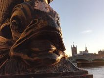 Gold fish near river Thames. Gold fish statue in front of river Thames and famous bridge. Architecture of London. Urban statue royalty free stock photo