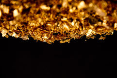 Gold flakes. Real 24k gold flakes on black background Royalty Free Stock Images