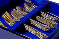 Gold Flatware. Closeup of a boxed set of gold plated flatware. Stacks of forks, spoons, and knives royalty free stock image