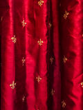 Gold fleur de lis on red silk curtains. Textured photograph of red curtains and gold fleur de lis symbols Stock Photography
