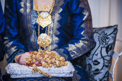 Gold flower on lap. View of a bouquet of flower made of gold on a lady's lap Stock Image
