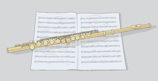 Gold flute. And note on grey background Royalty Free Stock Photo