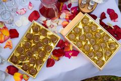 Gold box of assorted chocolates and rose stock photos