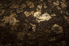 Gold foil on rock texture. Gold foil paste on a rock texture from a part of image of Buddha. This made form a lot of the faith of Buddhist Royalty Free Stock Photo