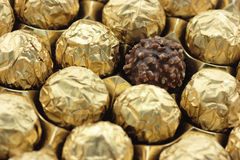 Gold foil on sweet chocolates. Chocolates wrapped in shiny gold metallic foil wrappers Stock Images