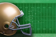 Gold football helmet against field diagram. Gold football helmet side view in front of a textured green field with a diagram of a play Stock Photo