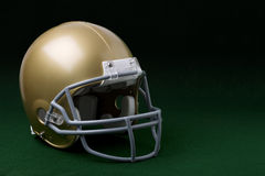 Gold football helmet on dark green background. A 3/4 view of a gold football helmet on a dark green background Stock Photography