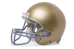 Gold football helmet on white background. A 3/4 view of a gold football helmet isolated on a dark green background royalty free stock image