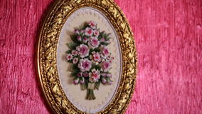 Gold frame with a bouquet of flowers. Gold oval frame with a bouquet of flowers on a red wall stock video