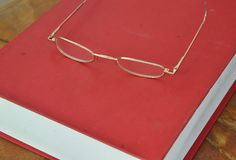 Gold frame eyeglass on red book Royalty Free Stock Image