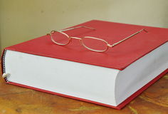 Gold frame eyeglass on red book Royalty Free Stock Photo