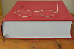 Gold frame eyeglass on red book Royalty Free Stock Images