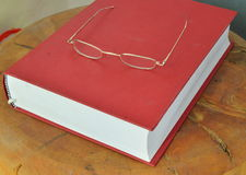 Gold frame eyeglass on red book Stock Photography