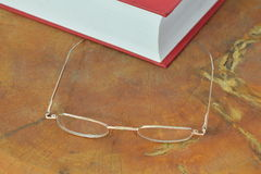 Gold frame eyeglass and red book Stock Photo