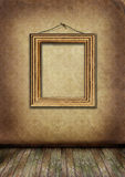 Gold frame hangs on an old wall. Royalty Free Stock Photo