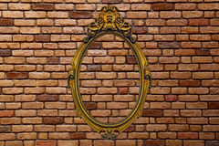 Gold frame on old brick wall Stock Images