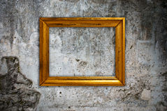 Gold frame on a old wall Stock Images