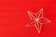 Gold frame star christmas decoration on red textile background. Copy space stock photography