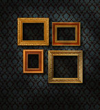Gold frames damask wall. Four gilded frames on dark blue damask pattern wall paper stock photo