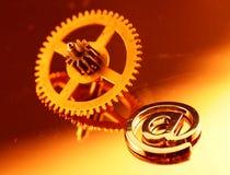 Gold gear old clockwork & e-mail. Metal alphabet symbol Royalty Free Stock Photo