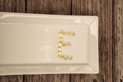 Gold gel capsule of vitamin E. Displayed on a white surface Royalty Free Stock Images