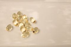 Gold gel capsule of vitamin E. Displayed on a white surface Royalty Free Stock Photos
