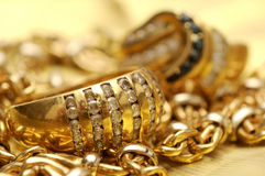 Gold and gems. Gold rings with gems over gold chain background