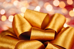 Gold gift bow with festive lights Royalty Free Stock Photos
