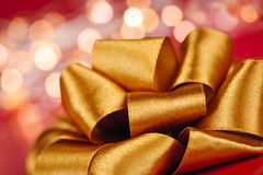 Gold gift bow with festive lights Stock Photography