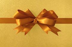 Gold gift bow ribbon, shiny metallic foil paper background, horizontal Stock Photo