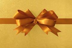 Gold gift bow ribbon, shiny metallic foil paper background, horizontal Stock Photo