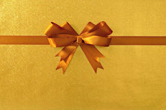 Gold gift bow ribbon, shiny metallic foil paper background, straight horizontal Royalty Free Stock Photos