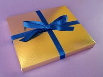 Gold gift box - 10. Close up view of a gold gift box with blue bow on violet background royalty free stock photo
