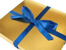 Gold gift box - 3. Close up view of a gold gift box with blue bow on white background stock photography