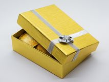 Gold gift box with golden coins stock image