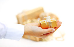 Gold gift box in hand with ribbon isolated on white backgraund Royalty Free Stock Image