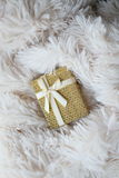 Gold gift box on a light fur rug Royalty Free Stock Photos