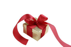 Gold Gift Box with Red Bow. Gold gift box with red satin ribbon and bow isolated on white background stock photography