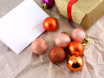 Gold gift box with red bow and christmas balls set on old paper Royalty Free Stock Images