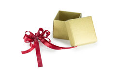 Gold gift box with red ribbon Stock Photos