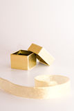 Gold gift box with the ribbon. Small gold gift box with the ribbon at the front Royalty Free Stock Photography