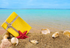 Gold gift box on sand and sea. Gold gift box on sand with summer sea background Royalty Free Stock Photo