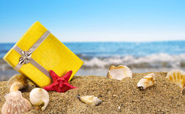 Gold gift box on sand and sea. Gold gift box on sand with summer sea background Royalty Free Stock Photography