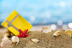 Gold gift box on sand with summer sea. Background Royalty Free Stock Photo