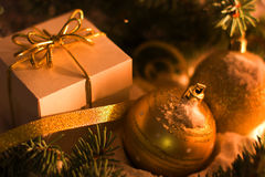 Gold gift box with silver bow, toy balls Stock Photos