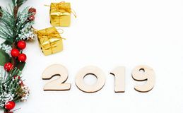 Gold gift boxes, decorative spruce branch and symbol numbers 2019 New year on white background, simple flatley Christmas card. stock images