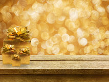 Gold gift boxes and ribbon on wood table, bokeh background. Gold gift boxes and ribbon on wood table Stock Photos